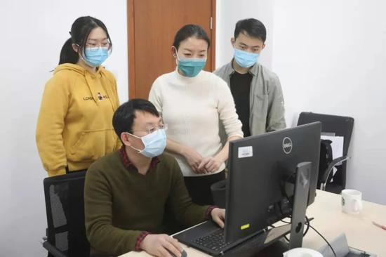 王小莉(后排中二)正在和同事们分析感染者分布特点。新京报记者王嘉宁 摄