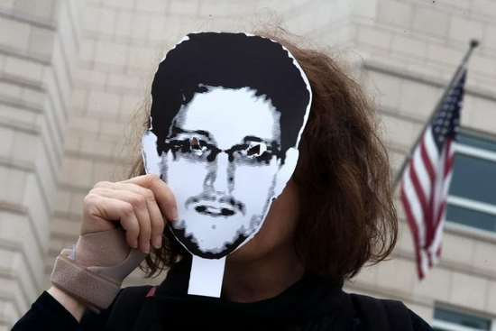 圖為一名抗議者手持斯諾登頭像站在美國駐柏林大使館前。新華社/路透