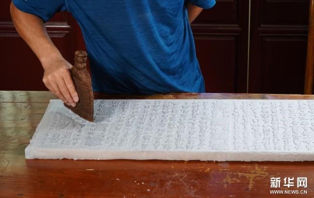 9月1日,衡水法帖雕版拓印技艺的代表性传承人李广民在拓印前用刷子找平。新华社记者 金皓原 摄