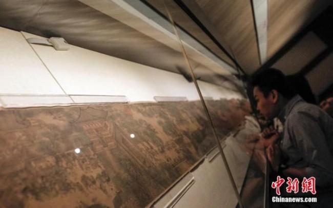 资料图:游客在北京故宫博物院观看石渠宝笈特展上的《清明上河图》。中新社发 张浩 摄