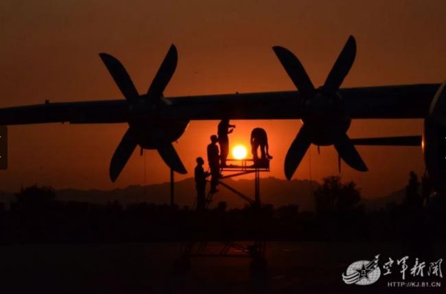 夕阳下,地勤人员对预警机进行维护作业。