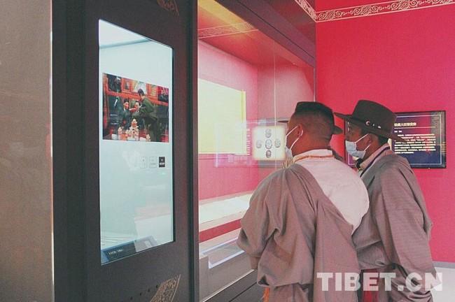 中国西藏网讯 9月26日,来自西藏自治区拉萨市尼木县的30名基层干部来到民族文化宫、西藏文化博物馆进行参观,一同了解西藏的历史,感受家乡的时代变迁。图为两名西藏基层干部在观看金瓶掣签动画演示。摄影:王茜